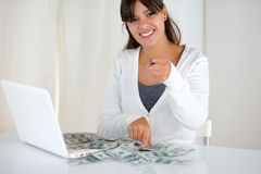 Young woman pointing at you with cash money. Portrait of a young woman pointing and smiling at you with cash money in front of laptop screen Stock Photography