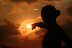 Young woman points out the sun. Back lit of young woman who points out with her finger the sun in a golden sunset background Royalty Free Stock Photo