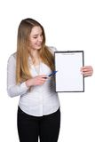 Young woman points to a clipboard with a pen Royalty Free Stock Image