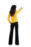 Young woman points at wall. Royalty Free Stock Images