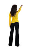 Young woman points at wall. The rear view Royalty Free Stock Images