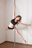 Young woman pole dancing. Beautiful young woman pole dancing in corner of room. Flying ballerina pose Royalty Free Stock Image