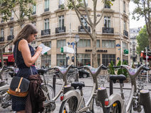 Young woman in polka dot dress reads map by Velib bicycles, Pari Royalty Free Stock Photos