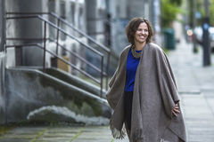 Young woman in a poncho at evening street. Happy. Royalty Free Stock Photo