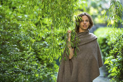 Young  woman in poncho among the green foliage in the garden. Royalty Free Stock Photography