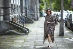 Young  woman in a poncho standing in the street near the house. Stock Photos