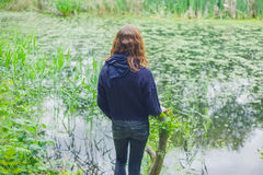 Young woman by pond in forest Royalty Free Stock Images