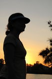 Young woman by pond at sunset. Expecting  - hopes and dreams.   Wife, serene and silhouetted at sunset by pond Stock Photo