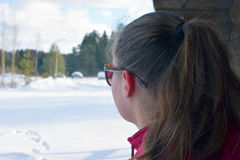 Young woman with ponytail watching winter landscape on her own thoughts. Close up Stock Photography