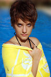 Young woman by the pool. Beautiful young woman, with a bath towel, close to a swimming pool royalty free stock image