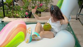 Young woman in pool chilling and making selfie. Close-up of woman portrait smiling and drinking a long cocktail from coconut fruit on exotic island resort stock video