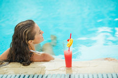 Young woman at pool with cocktail. rear view Stock Photos