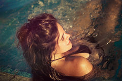 Young woman in pool enjoy in warm sun real people concept. Young smiling woman in pool enjoy in warm sun lean on pool edge  real people concept Royalty Free Stock Images