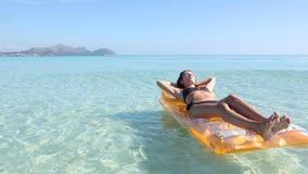Young woman on pool raft Stock Photo