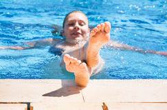 Young woman in the pool shows feet.  Stock Image