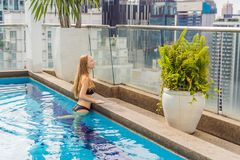 Young woman in the pool among the skyscrapers and the big city. Relax in the big city. Rest from stress royalty free stock images