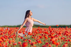 Young woman in poppy field in evening time Stock Photo