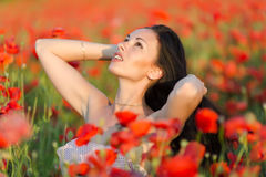 Young woman in poppy field Royalty Free Stock Photos