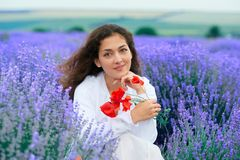 Young woman with poppy is in the lavender flower field, beautiful summer landscape stock photo