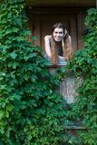 Young woman on the porch of a village house among greenery. Stock Photography