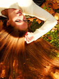 Young woman portrait in autumnal leaves. Fall lifestyle concept, harmony freedom. Woman portrait in autumn leaves. Girl with long hair having fun outdoor stock photo