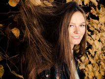 Young woman portrait in autumnal leaves. Fall lifestyle concept, harmony freedom. Woman portrait in autumn leaves. Girl with long hair having fun outdoor royalty free stock photography