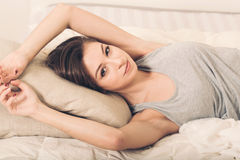 Young woman portrait in bedroom on bed alone relaxing Stock Image