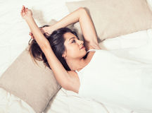 Young woman portrait in bedroom on bed alone relaxing Stock Images
