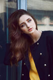 Young woman portrait in black trenchcoat and yellow blouse Royalty Free Stock Image