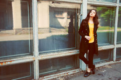 Young woman portrait in black trenchcoat and yellow blouse Stock Image