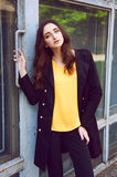 Young woman portrait in black trenchcoat and yellow blouse. Young woman portrait with long brown hair dressed in black trenchcoat and yellow blouse Stock Photography