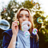 Young woman portrait blowing soap bubbles Royalty Free Stock Photo