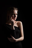 Young woman portrait in dark. Low key portrait of a young woman with side lighting royalty free stock image
