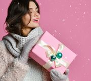 Young woman portrait hold gift. Smiling happy girl on pink background. royalty free stock photo