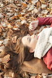 Young woman portrait lying on leaves, top view. Young woman portrait lying on leaves, hair spread, top view royalty free stock images