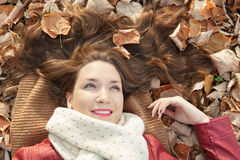 Young woman portrait lying on leaves, top view. Young woman portrait lying on leaves, hair spread, top view royalty free stock photo