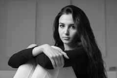 Young woman portrait. Pensive young girl sitting and posing, she is staring at camera Stock Image