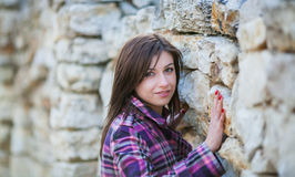 Young woman portrait. Young woman in sunshine portrait, looks straight to you, near the stone wall with big rocks Stock Images