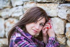 Young woman portrait. Young woman in sunshine portrait, looks straight to you, near the stone wall with big rocks Stock Photos