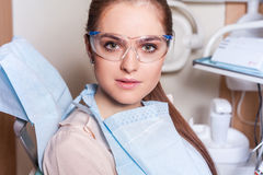 Young woman portrait visiting the dentist. She is ready for surg Royalty Free Stock Photo