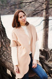 Young woman portrait on the walk in autumn forest in beige coat Stock Photos