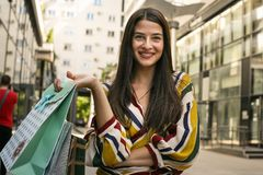 Young woman poses with bags after shopping. Looking at camera Stock Photography