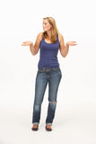 Young woman poses with shrugged shoulders Royalty Free Stock Photo