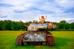 Young woman posing on army tank. Royalty Free Stock Photos