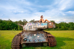 Young woman posing on army tank. Beautiful young woman meditating at sunset, on army tank Stock Images