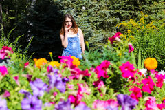 Young woman posing on the background, the foreground flowers.  royalty free stock image