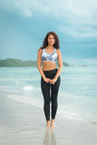 Young woman posing on the beach in sportswear. Female model on the sea shore. Stock Photo