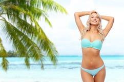 Young woman posing in bikini on beach royalty free stock photos