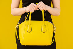 Young woman posing in black dress and yellow handlbag Stock Photos