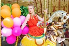Young woman posing on a carousel Stock Photos